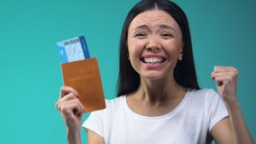 Excited Asian lady holding passport and flight tickets, work abroad, emigration. Stock footage stock video footage