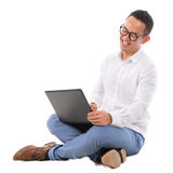 Excited Asian male using laptop. Full length of excited Asian businessman looking at laptop sitting over  white background Royalty Free Stock Photo