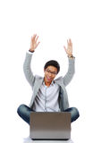 Excited Asian man using laptop on the floor. Over white background Royalty Free Stock Images