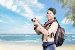 Excited asian tourist woman using camera to taking a photos Royalty Free Stock Photo