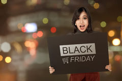Excited asian woman holding banner with Black Friday announcemen. T against blurred light background Royalty Free Stock Image