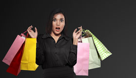 Excited asian woman holding colorful paper bag celebrating Black. Friday over black background Stock Photos