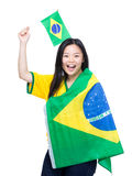 Excited asian woman holding and draping with Brazil flag Stock Photo