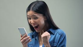 Excited Asian woman holding smartphone, playing mobile game, happy about winning. Stock footage stock video footage