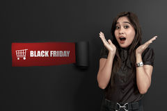 Excited asian woman with shopping cart and Black Friday text. On ripped paper Royalty Free Stock Photos