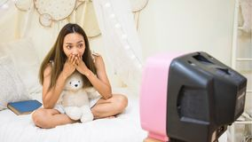 Excited Asian woman watch horror movie on bed. Excited Asian woman on the bed watch horror movie on antique tv and hold bear doll with frightened or shock Stock Images
