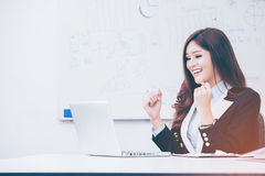 Excited Asian Woman. Working in her office Royalty Free Stock Images
