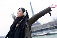 Excited asian young woman listening to music and enjoying moment in front of Eiffel tower in Paris. Shot of excited asian young woman listening to music and Stock Photography