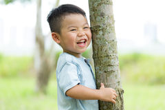 Excited Baby boy hold with tree bark. Asian young little boy at outdoor royalty free stock image