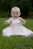 Excited baby discovers grass. A cute little girl in pink grass with excited, happy expression stock images