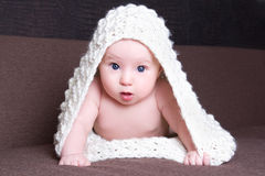 Excited baby girl in white woolen scarf crawling Stock Image