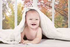 Excited baby laughing on bedroom Stock Images