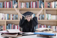 Excited bachelor studying in library Stock Images