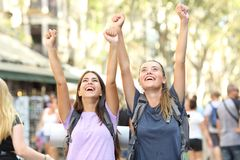 Excited backpackers celebrating vacation. Excited backpackers celebrating summer vacation in the street of a big city stock photography
