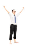 Excited barefooted guy with raised hands gesturing happiness Stock Photography