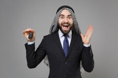 Excited bearded arabian muslim businessman in keffiyeh kafiya ring igal agal classic black suit isolated on gray