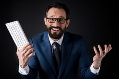 Excited bearded businessman in eyeglasses holding keyboard and looking at camera. Isolated on black Royalty Free Stock Photo