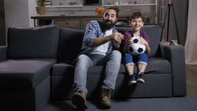Excited dad and son watching soccer on tv at home stock footage