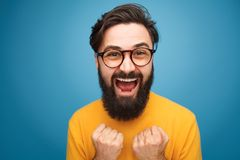 Excited bearded man in glasses. Excited handsome bearded man in glasses posing on blue background Stock Photo