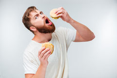Excited bearded man greedily eating hamburgers Royalty Free Stock Photo
