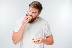 Excited bearded man greedily eating hamburgers Royalty Free Stock Image