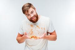 Excited bearded man holding slice of pizza on his palms Stock Photography