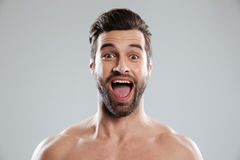 Excited bearded man with naked shoulders and open mouth. Portrait of an excited bearded man with naked shoulders and open mouth isolated over white background royalty free stock photography