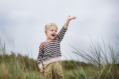 Excited beautiful boy puts up his hand and screaming. Oudoor portrait Royalty Free Stock Image
