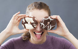 Excited beautiful girl holding donuts on her eyes for joke Stock Images