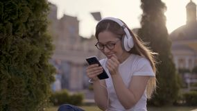 Excited beautiful girl receiving a sms message with good news in a mobile phone outside in a park with a green stock footage