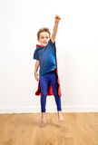 Excited beautiful little boy dressed like a powerful superhero jumping Royalty Free Stock Image