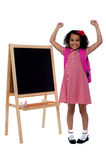 Excited beautiful little girl in school uniform Stock Photos