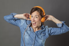 Excited beautiful middle aged woman laughing with funky music on Royalty Free Stock Images