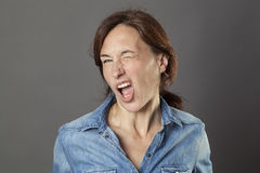 Excited beautiful middle aged woman winking for cheeky modern seduction. Excited beautiful middle aged woman enjoying winking, making a funny face for cheeky Royalty Free Stock Photo