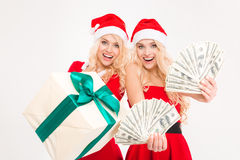 Excited beautiful sisters twins showing money and gift Stock Photography