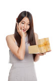 Excited beautiful young Asian woman with golden gift box Stock Photo