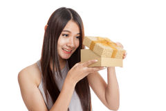 Excited beautiful young Asian woman with golden gift box Stock Photos