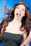 Excited Beautiful Young Woman on blue. Beautiful Young Woman with widely open mouth in Excitement on blue background Royalty Free Stock Photography