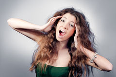 Excited Beautiful Young Woman with open mouth. Beautiful Young Woman with widely open mouth in Excitement on gray background Stock Photos