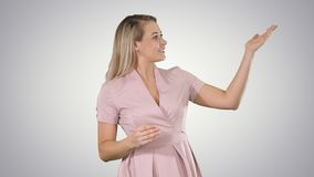 Excited beautiful young woman in pink dress talking to camera on gradient background. royalty free stock images