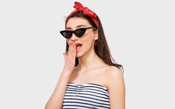 Excited beautiful young woman wears striped blouse, black trendy sunglasses and red headband, looking to camera. Isolated on white studio background. Girl with stock photography
