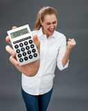 Excited beautiful young woman winning money in holding symbolic calculator Royalty Free Stock Photography