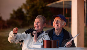 Excited Bird Watchers. Happy elderly bird watchers outside in jackets stock photo