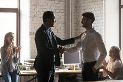 Excited black boss handshake male employee greeting with success royalty free stock images
