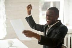 Excited black businessman enjoying good news about promotion in. Excited happy black businessman enjoying good news about promotion in written notice, african stock photos