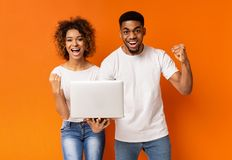 Excited black couple celebrating win with laptop royalty free stock photos