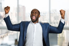 Excited black entrepreneur clenching his fists. Shouting with joyful young entrepreneur raised hands. Expression of goal achievement with raised arms Royalty Free Stock Photography