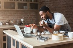 Excited black man baking and looking recipe on laptop stock photo
