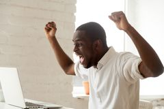 Excited black manager celebrating online win. Excited amazed black worker throwing hands up, screaming celebrating online win, earning money, reaching goal royalty free stock photos