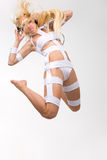 Excited blond model with headphones jumping stock images